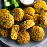 close up of a pile of crispy baked falafel on a gray plate with side of dip
