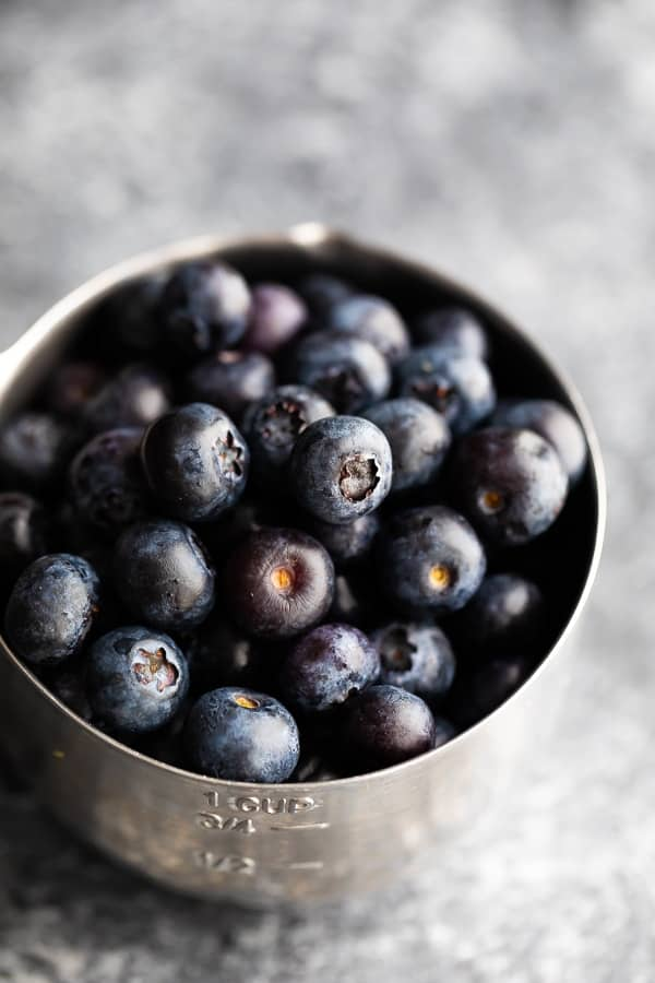 blueberries in measuring cup for the lemon blueberry bread