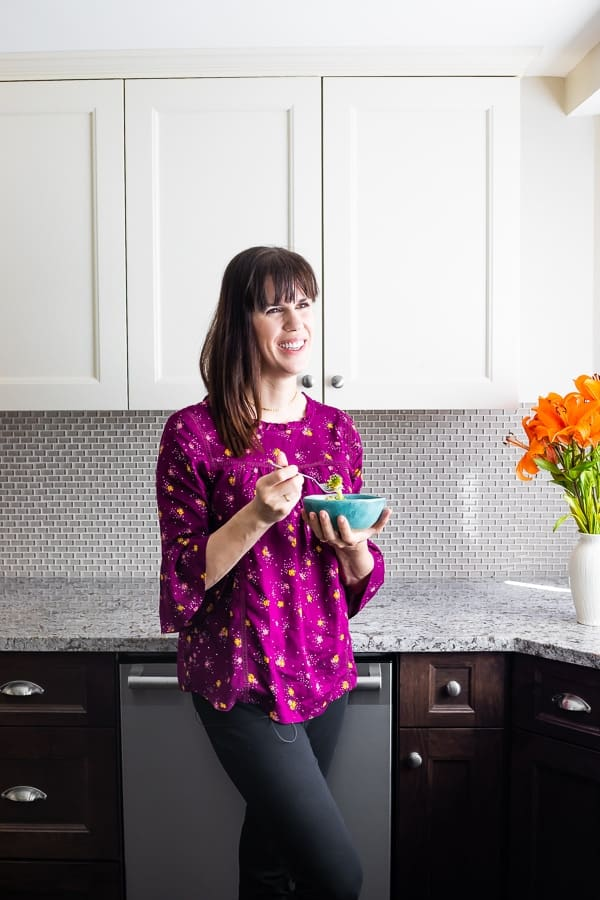Photo of Denise standing in her kitchen eating out of a blue bowl