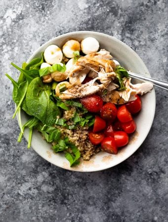Overhead shot of caprese chicken quinoa salad on gray background