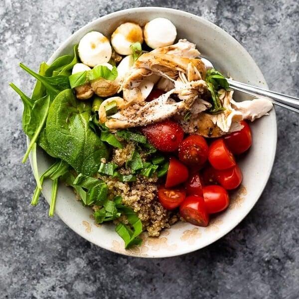 Overhead shot of caprese chicken quinoa salad on gray background