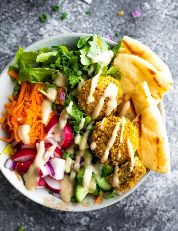 overhead shot of a falafel salad bowl with pita bread and dressing drizzled on top