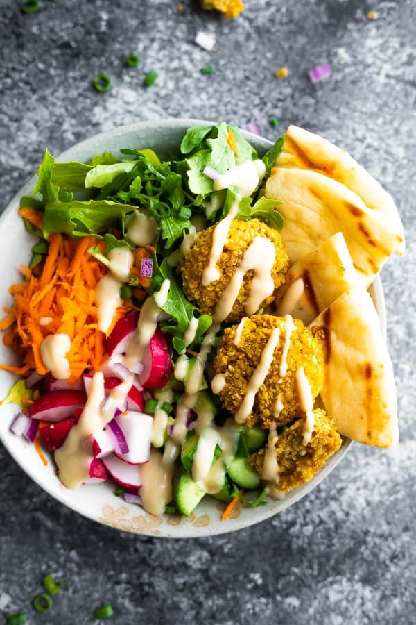 overhead view of falafel salad bowls drizzled with tahini sauce