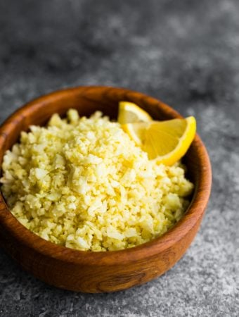 Lemon garlic cauliflower rice in a wood bowl with lemon slice garnish