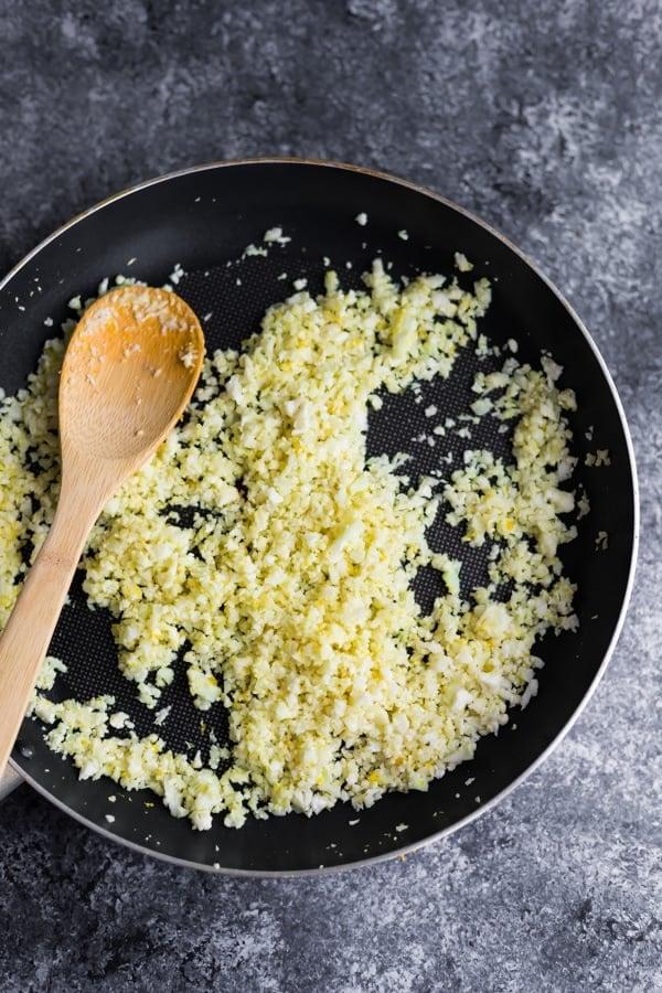 cooking lemon cauliflower rice in pan