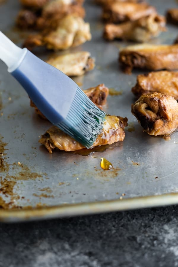 brushing the cooked slow cooker chicken wings with maple syrup before broiling