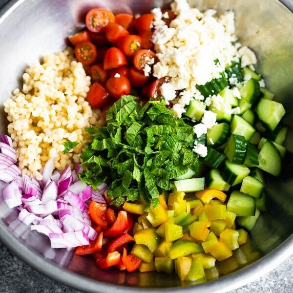 Large mixing bowl with all the ingredients for summer couscous salad