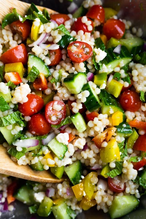 close up of mediterranean couscous salad tossed in dressing