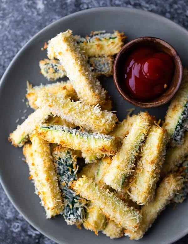 overhead shot of crispy baked zucchini fries on gray plate with small bowl of ketchup