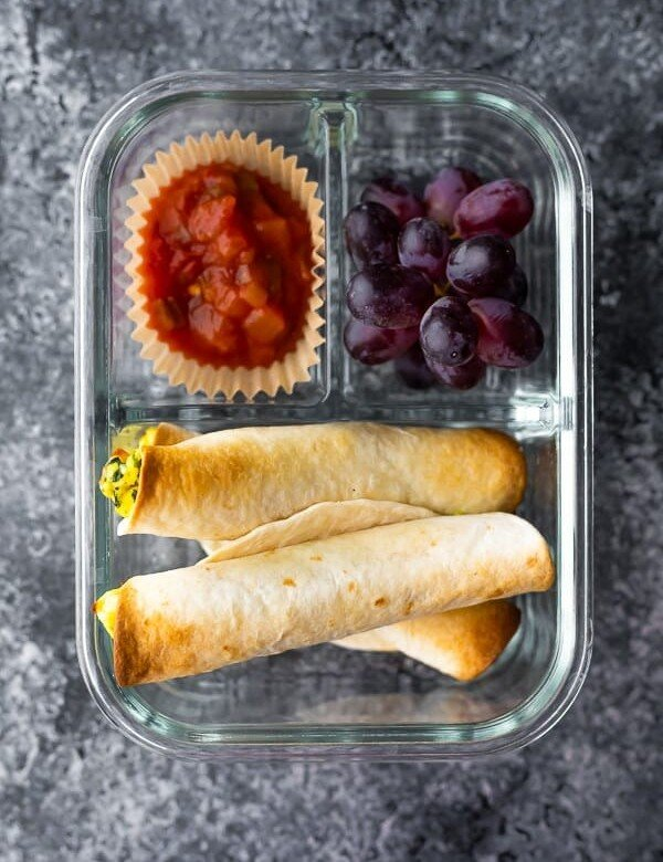 overhead shot of breakfast taquitos in a meal prep container with a side of salsa and grapes