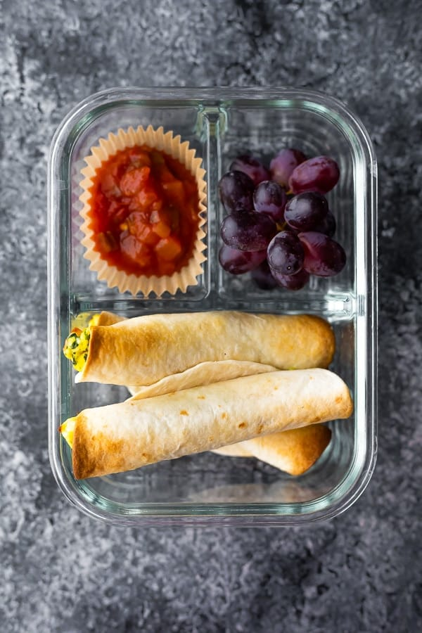 breakfast taquitos in meal prep container with eggs and salsa