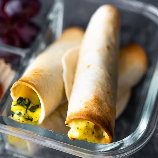 Three breakfast taquitos in a glass meal prep container