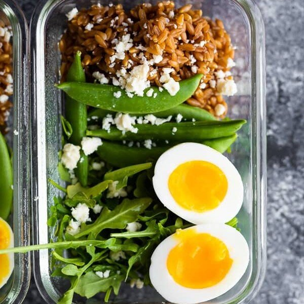 overhead shot of farro arugula salad with a soft boiled egg in glass meal prep container