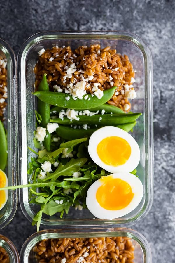 overhead view of arugula salad with farro and eggs in meal prep container