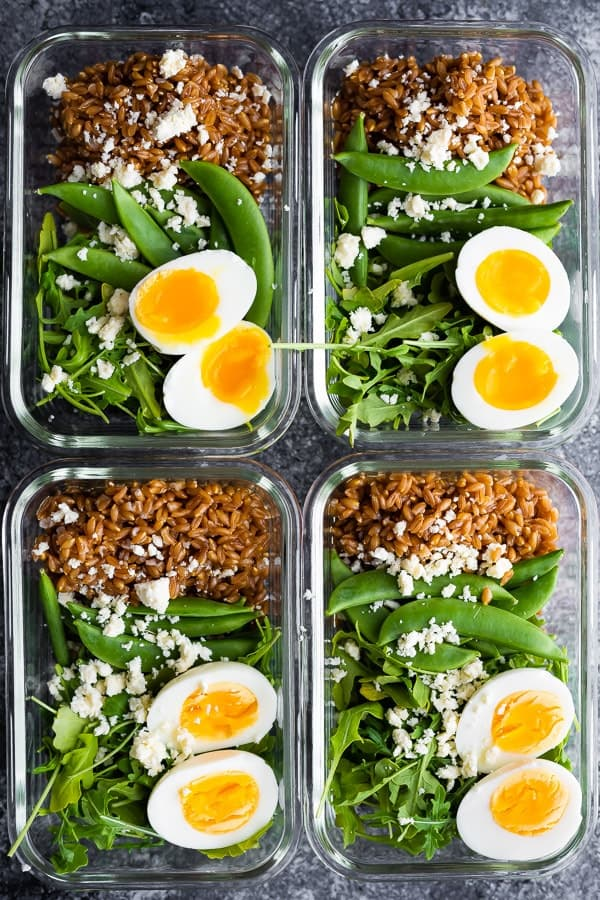 four meal prep containers with salad tossed in arugula salad dressing