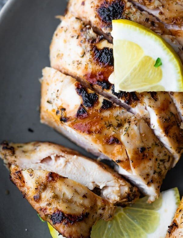 Sliced chicken with greek marinade on gray plate with a lemon slice