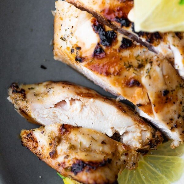close up shot of sliced chicken with greek marinade and lime slices
