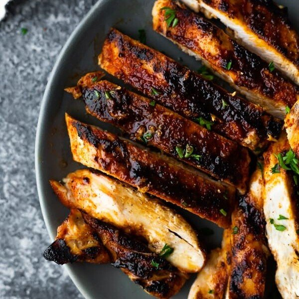 overhead shot of sliced grilled chicken breast on gray plate