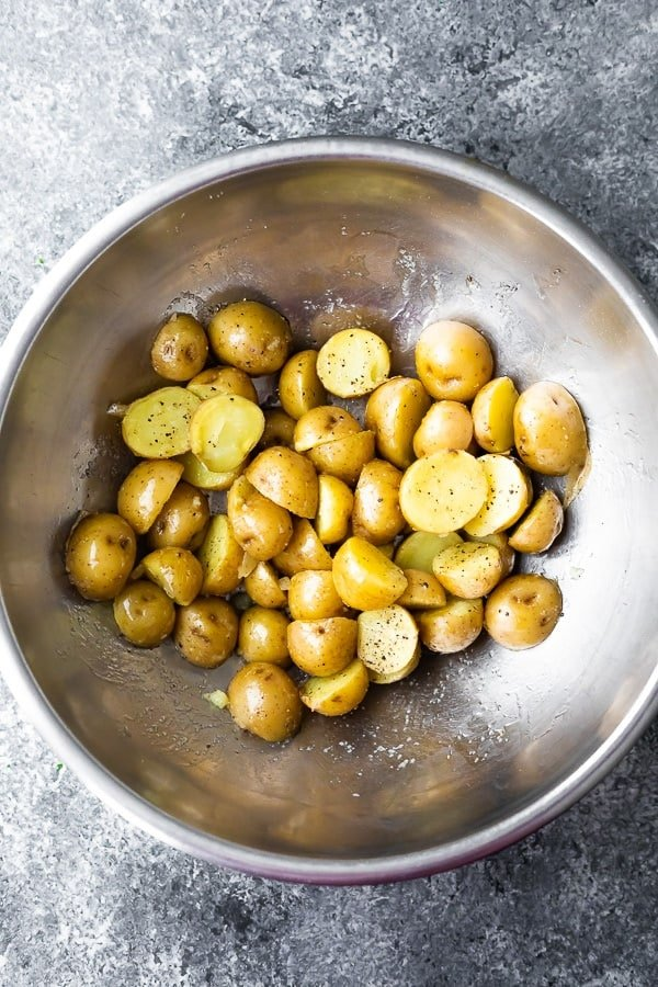 how to grill potatoes- tossing potatoes in olive oil before grilling
