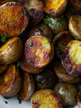 Close up shot of crispy grilled potatoes with parsley sprinkled on them