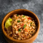 wood bowl filled with mexican cauliflower rice and lime wedges
