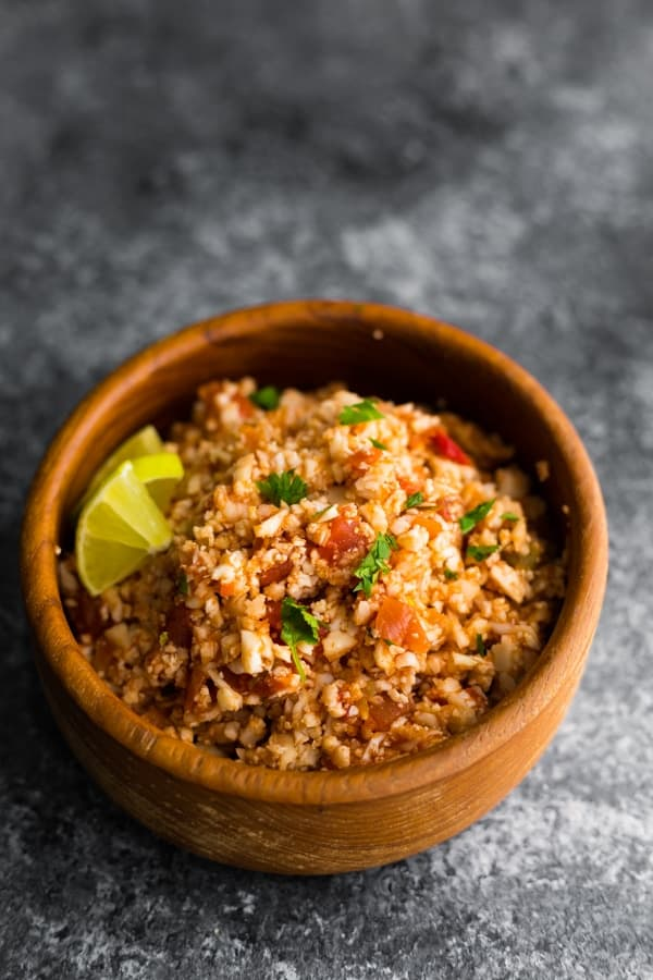 side angle view of mexican cauliflower rice in wooden bowl