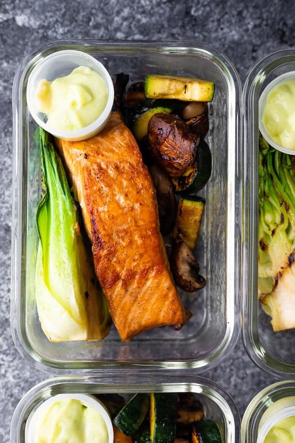 glass container filled with wasabi grilled salmon bowls and sauce