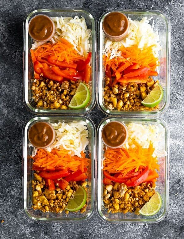 overhead shot of four glass containers filled with tofu spring roll bowls