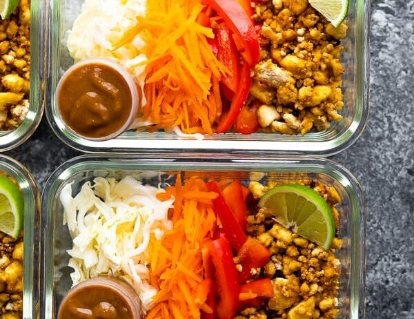 overhead shot of tofu spring roll bowls in glass containers with lime wedge and dressing