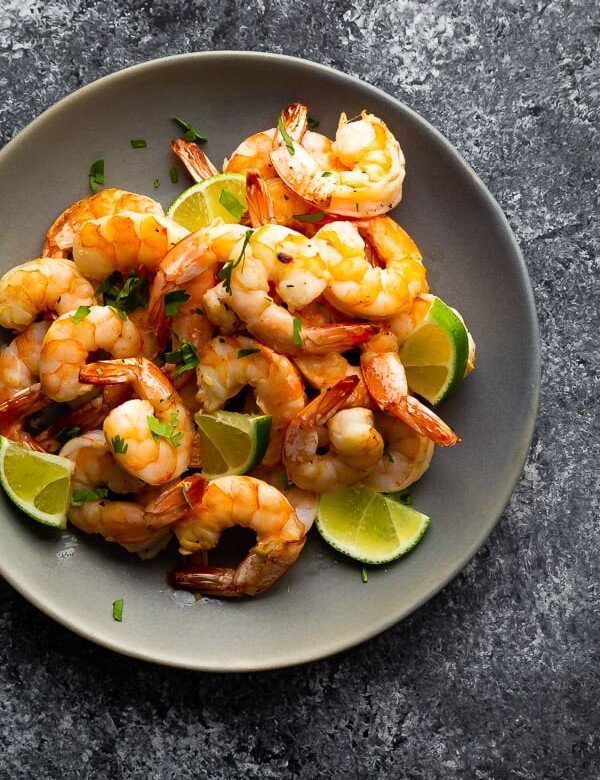 overhead shot of a pile of honey lime shrimp in gray bowl with fresh lime slices