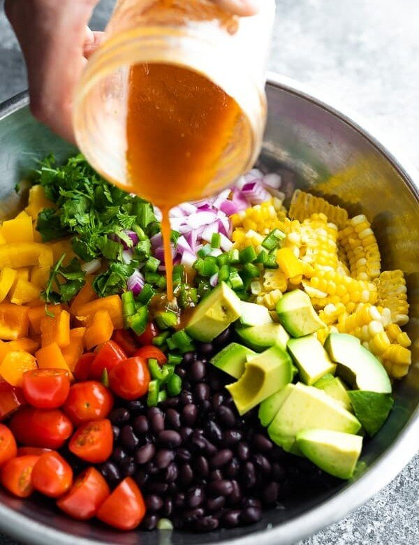 dressing being poured out of a mason jar over black bean and corn salad in large metal bowl