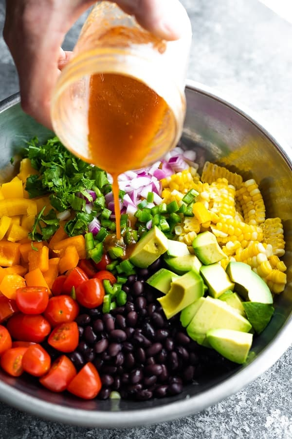 pouring dressing on black bean and corn salad