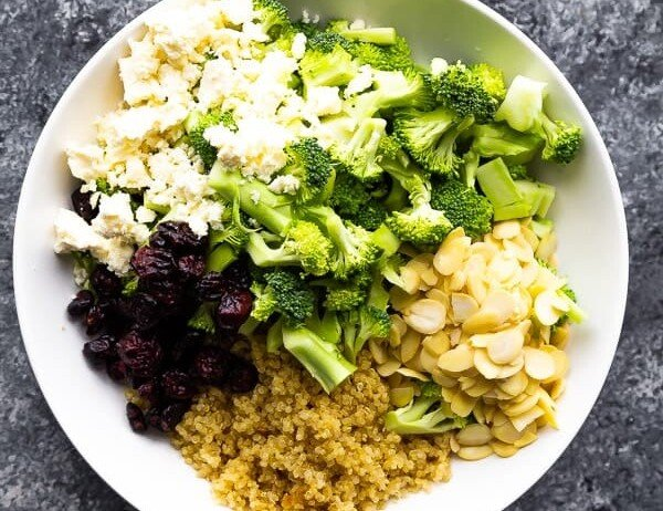 overhead shot of broccoli quinoa salad with almonds in white bowl