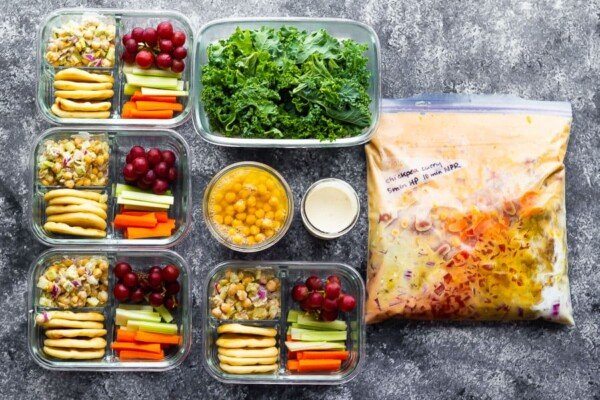 overhead shot of variety of foods in meal prep containers and freezer bag