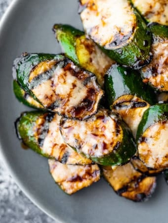 balsamic grilled zucchini with parmesan in a pile on gray plate