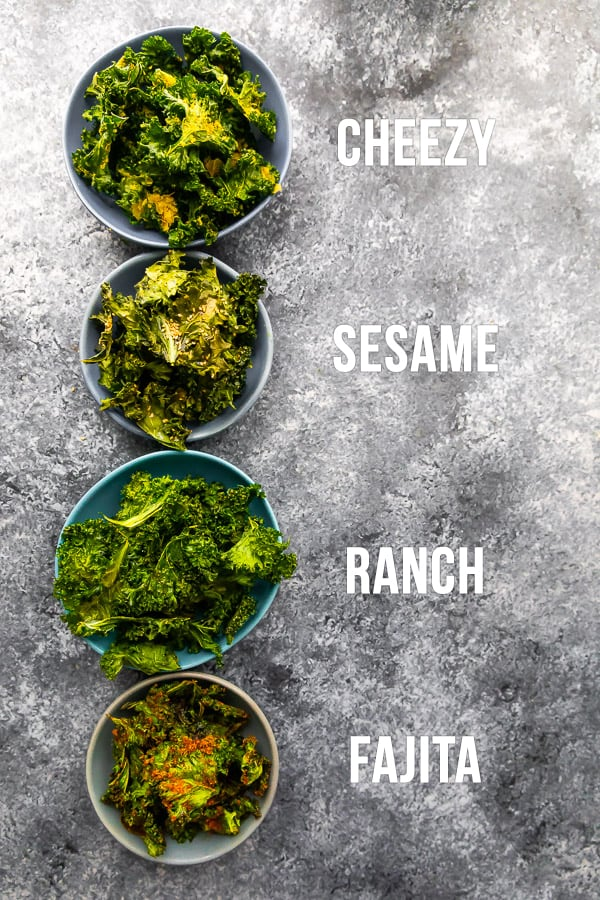 overhead view of four bowls of baked kale chips with different seasonings