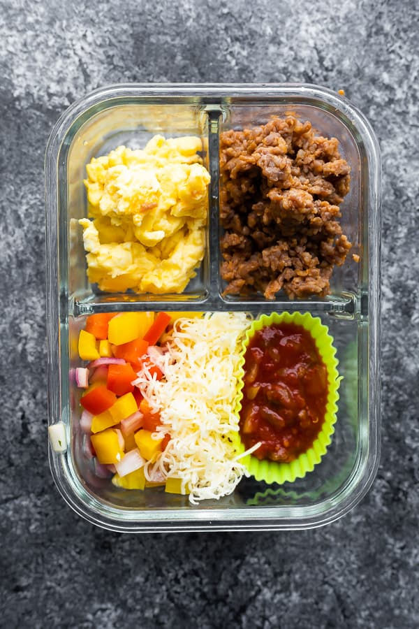 overhead view of breakfast tacos ingredients in meal prep container