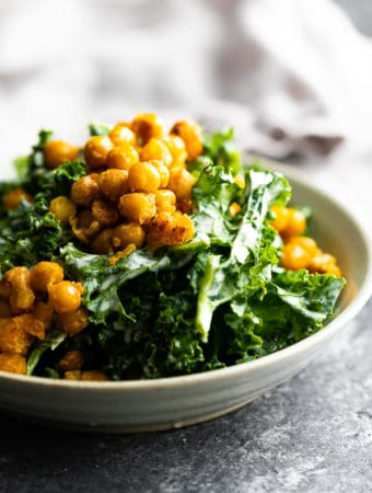 side view of kale caesar salad with garlic chickpeas in gray bowl