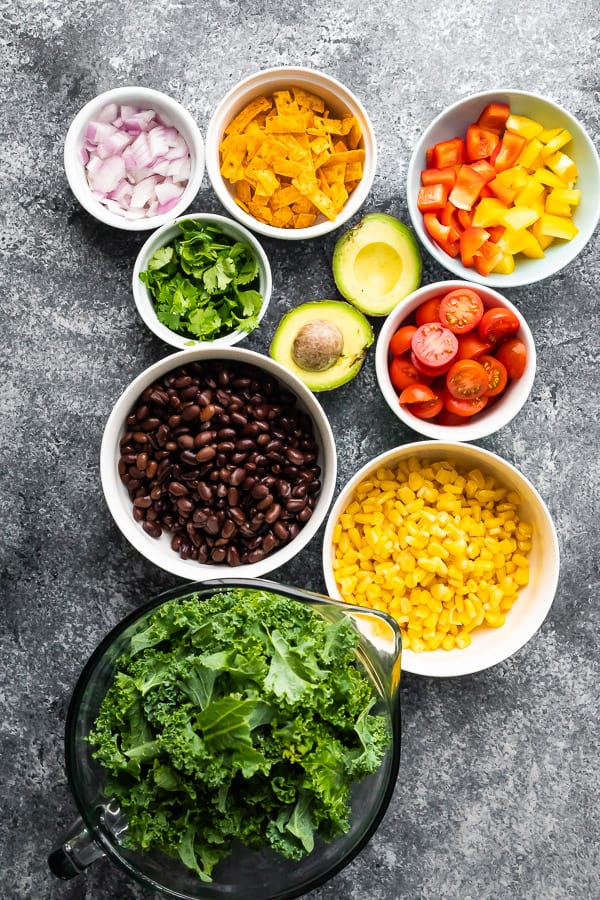 overhead view of chopped kale salad ingredients in bowls
