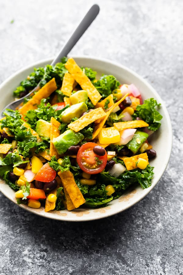 mexican kale salad in grey bowl after tossing it up