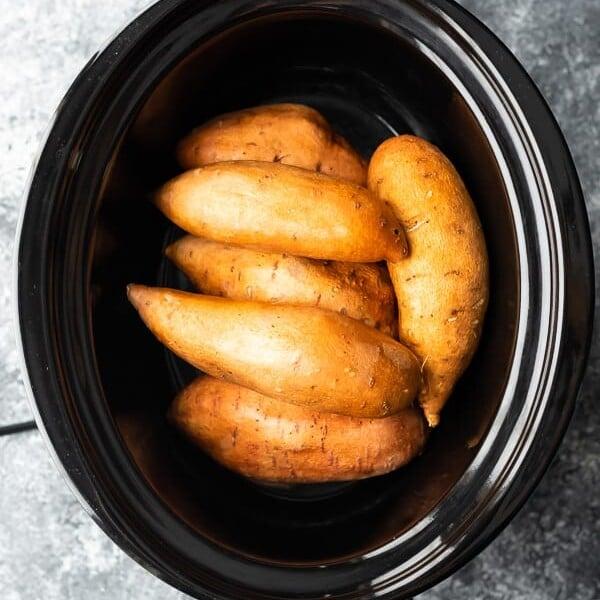 overhead shot of whole sweet potatoes in crock pot