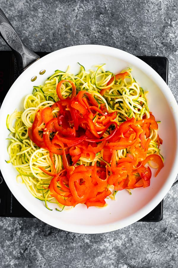 overhead view of spiralized zucchini and bell pepper in frying pan