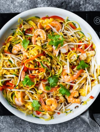 overhead shot of zucchini noodle pad thai in large white bowl