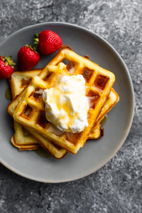 overhead shot of crispy buttermilk waffles with syrup and fresh strawberries