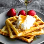 stack of three buttermilk waffles on a gray plate with syrup being drizzled over them and fresh strawberries