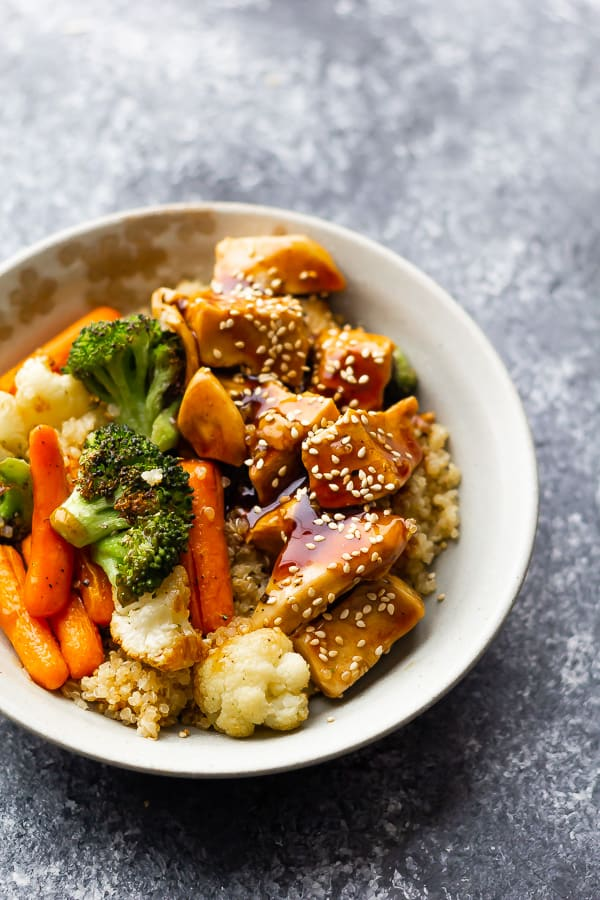 white bowl with roast veggies and chunks of chicken over quinoa