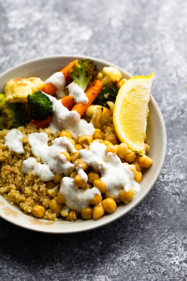 white bowl with chickpeas, roast veggies, white sauce and fresh lemon