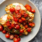 overhead shot of baked bruschetta chicken with cherry tomatoes on gray plate
