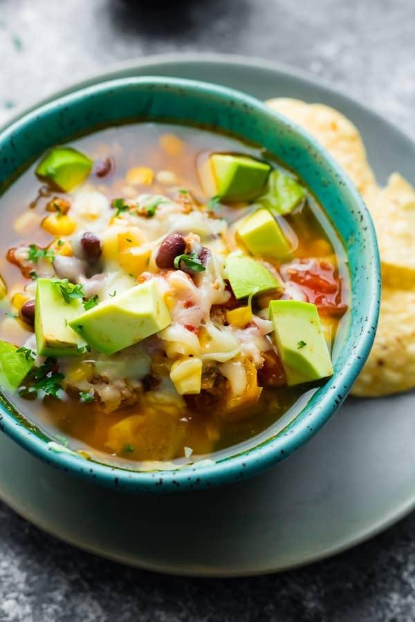 close up of taco soup crockpot recipe in blue bowl