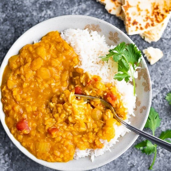 overhead shot of rice and red lentil dal in a white bowl with a fork and fresh cilantro